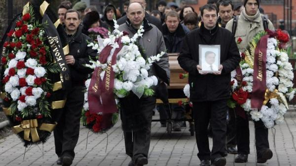 Friends and relatives take part in the funeral ceremony of Sergei Magnitsky at a cemetery in Moscow in 2009. The tax lawyer was arrested after he began investigating fraud at Hermitage Capital, which had been seized by the Russian tax police. He later died in prison.