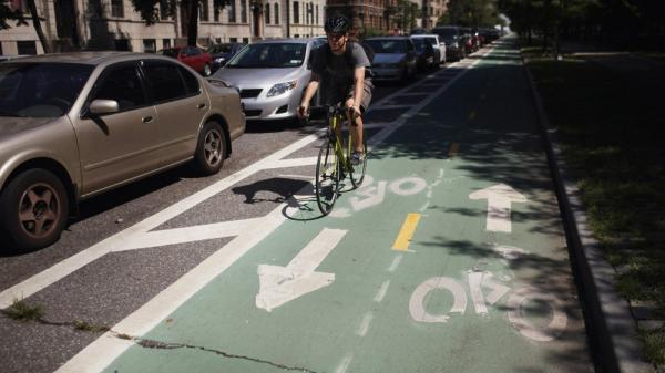 A cyclist rides on a bike lane on Prospect Park West, in the Brooklyn borough of New York City. Bike lanes of this type use parked cars to create a buffer zone from road traffic.