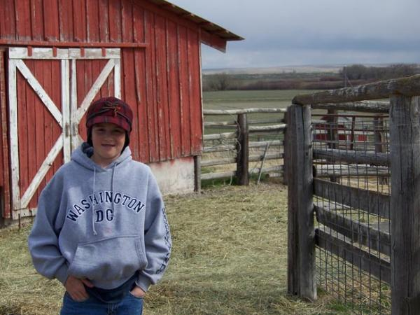Kirk Eiguren, 12, of Arock, Ore., doesn't mind helping his littler brothers with their chores like feeding the pigs and brining in the calves – too much. Photo by Anna King