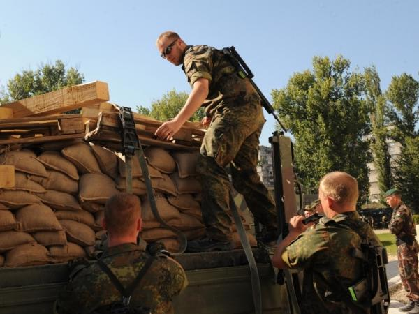 German troops serving in the NATO-led peacekeeping mission (KFOR) in Kosovo unload sandbags as part of the reinforcement of KFOR troops in the town of Mitrovica on September 28, 2011.
