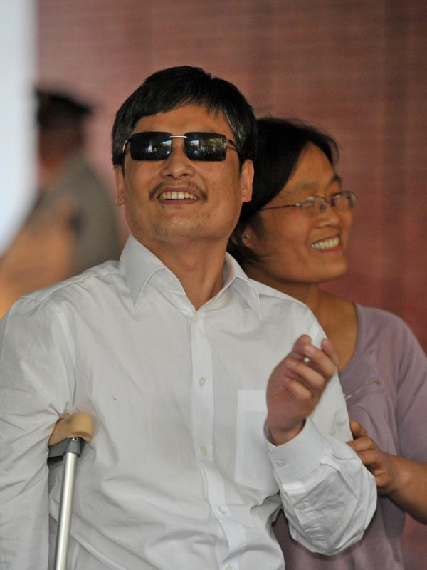 Chinese activist Chen Guangcheng and his wife, Yuan Weijing, arrive at an apartment complex in New York on Saturday. A number of Chinese activists have become far less prominent after leaving their homeland, but Chen hopes to continue his work and remain relevant in China.
