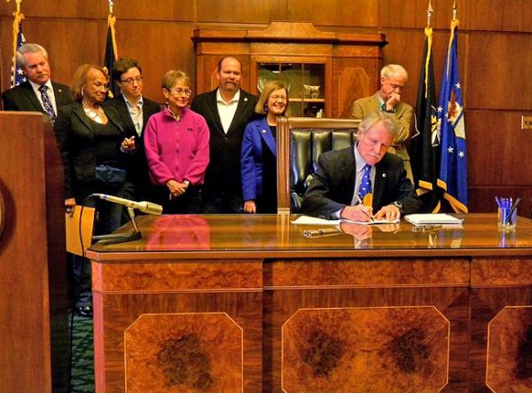 File photo of Oregon Governor John Kitzhaber signing two measures into law in March. Photo by Chris Lehman
