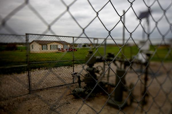 A working gas well head is fenced in just opposite a home. Dish is about 30 miles north of Fort Worth.