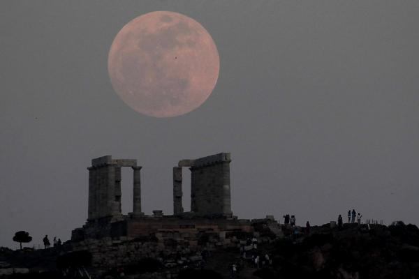 Tourists look at the moon rising over the ancient temple of Poseidon at cape Sounion, south of Athens.