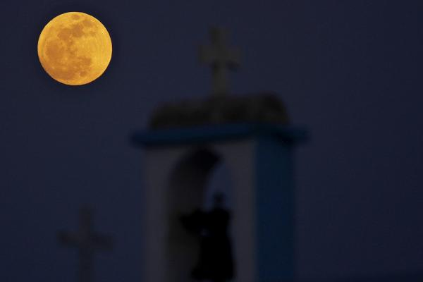 The full moon rises behind a steeple with cross of Ayia Thekla (Saint Thekla) Christian Orthodox church near coastal resort of Ayia Napa, Cyprus.