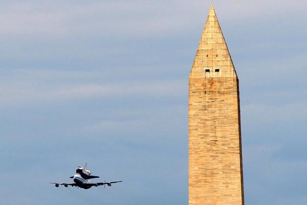 Space shuttle Discovery, mounted atop a 747 shuttle carrier aircraft, flies by the Washington Monument during a flyover of the nation's capital.