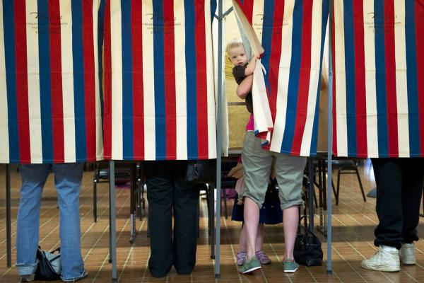 Landon Peterson peeks out of the voting booth while his mother, Meghan, votes in Metamora, Ill.
