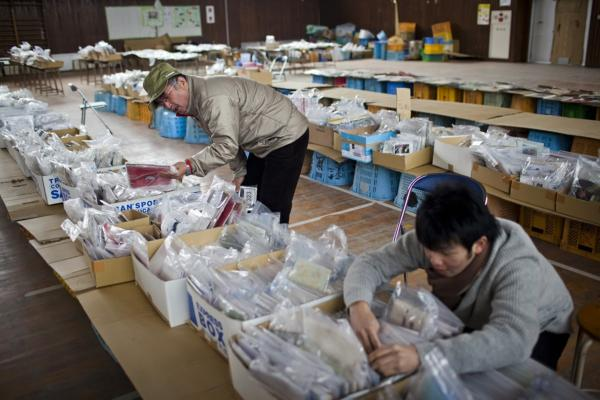 Daisuke Arakawa (right) searches for a photograph of his grandparents, with his uncle Katsuhiko Arakawa, in a school gym set up as a collection site for articles found after the tsunami, in the Yuriage area of Natori, Japan.
