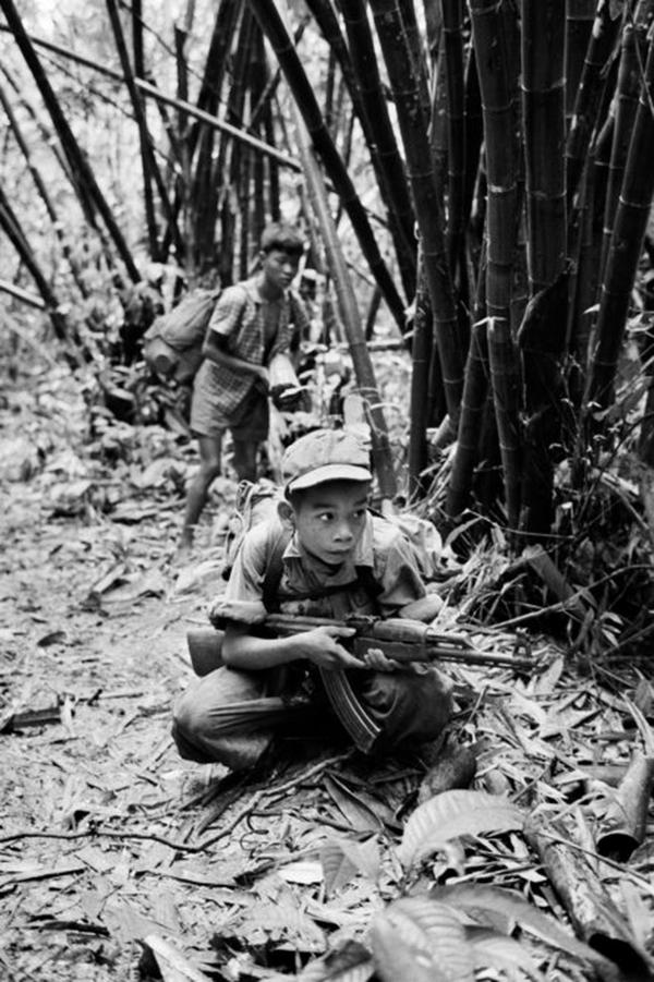 A 14-year-old Vietnamese boy points an AK-47 in 1968. The Vietnam War became the first large conflict in which both sides carried assault rifles.