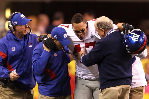 Giants tight end Travis Beckum gets assisted off the field after injuring his ACL.