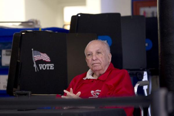 A polling official waits for voters in Miami.