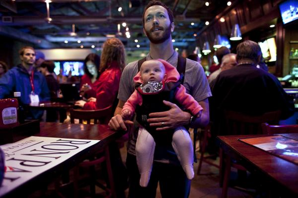 Kenny Ball holds his daughter, McKenna, while watching primary returns at Ron Paul's primary night campaign rally in Columbia.