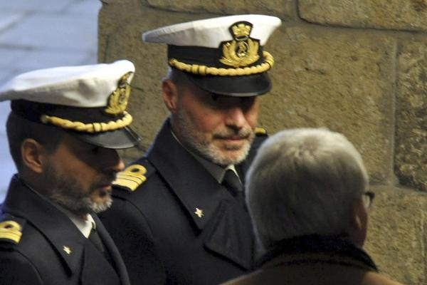 Coast Guard Capt. Gregorio De Falco (center) arrives Tuesday at the Grosseto court in Italy for a hearing. In a dramatic phone conversation, De Falco was heard ordering Francesco Schettino, the captain of the stricken cruise liner, to get back onboard and oversee the evacuation.