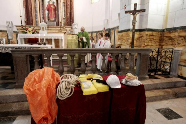 A rope, a life vest, a helmet and other recovered items are displayed on an altar during Mass in Giglio on Sunday.