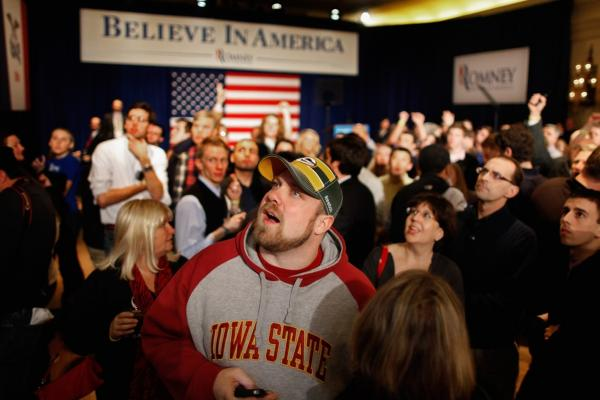 Supporters and volunteers watch caucus results during a rally for Mitt Romney in Des Moines.