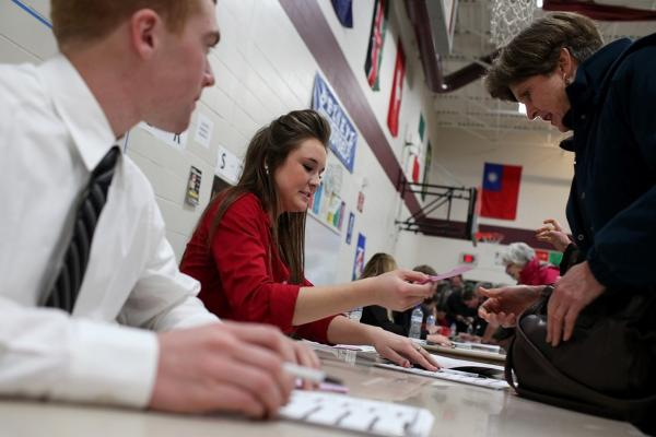 Kate Paul (center) registers a caucusgoer at the Ankeny 9 Republican caucus in Ankeny.