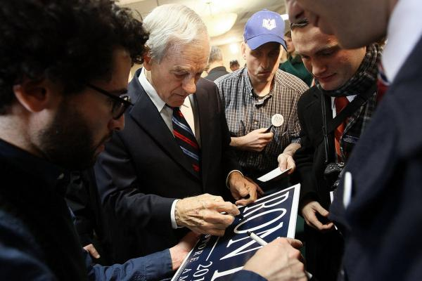 "U.S. Rep. Ron Paul of Texas signs autographs for supporters after a campaign event during his ""Whistle-stop"" tour at the Steeple Gate inn Monday in Davenport, Iowa."