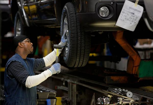 Ken Grady puts tires on trucks on the Ford Ranger production line.