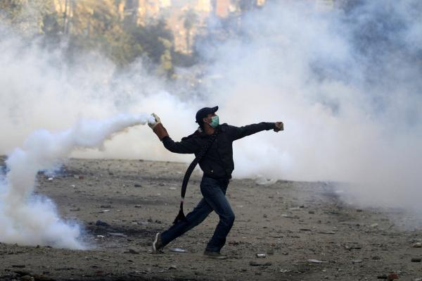 A protester throws a tear gas canister during battles with riot police in Tahrir Square.