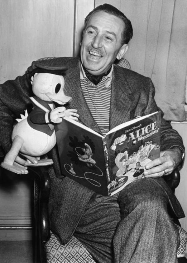 <b>Walt Disney: </b> Revolutionized animation and inspired iconic characters, stories and Walt Disney Co. theme parks that have become a permanent fixture in popular culture. Disney posed with a Donald Duck character while reading from Alice in Wonderland during a 1951 movie premiere in London.