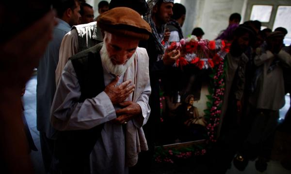 An Afghan man prays over Massoud's grave. Even today, posters of Massoud still adorn shops in the country's north.