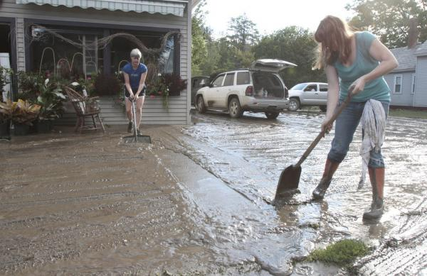 Nina Brennan (right) and Phyllis Berry clean mud away from the front of the Proud Flower store in the aftermath of Tropical Storm Irene on Monday, Aug. 29, 2011 in Waterbury, Vt.