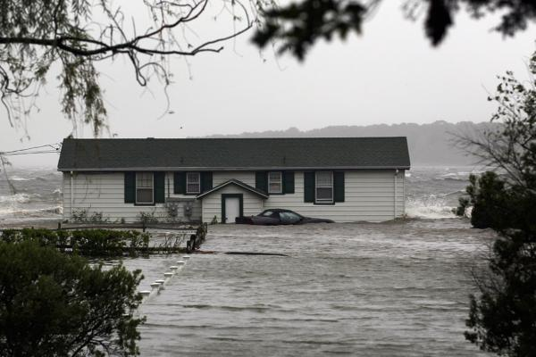 Waves crash around a home Sunday morning in Southampton, N.Y.