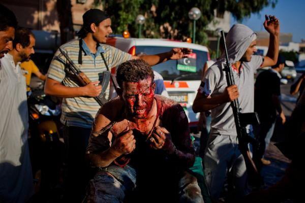 Libyan rebel fighters protect a pro-Gadhafi fighter from angry onlookers as he is brought in for medical attention to the Tripoli Central Hospital following heavy fighting Aug. 25.