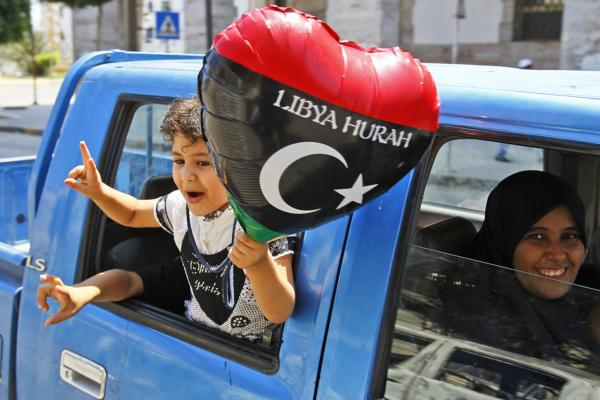 A Libyan family shows support for the rebel forces as they drive in a safe district in Tripoli.
