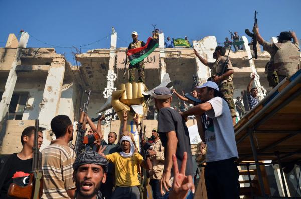 Rebels celebrate around the iconic statue of a golden fist crushing a U.S. military bomber in Tripoli on Wednesday.