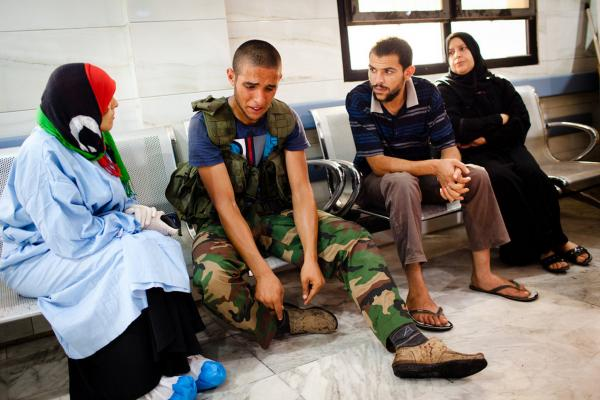 A rebel soldier reacts after a fellow fighter was brought in with a wound sustained in battle with fighters loyal to longtime leader Moammar Gadhafi at Tripoli Central Hospital.