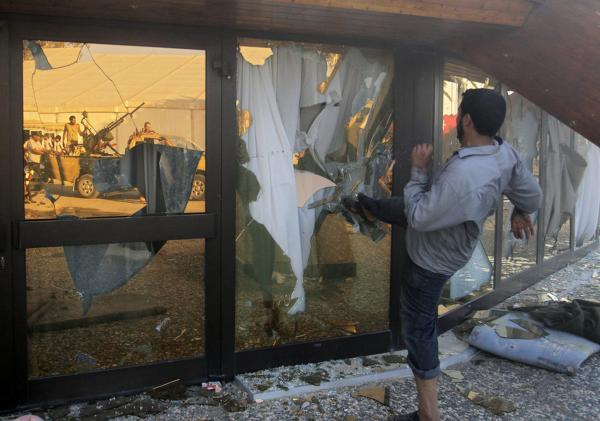 A Libyan rebel breaks the glass of Gadhafi's main compound in Tripoli.