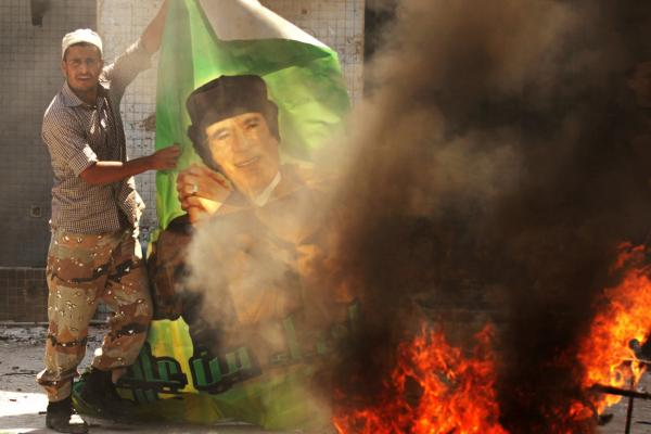 A Libyan rebel burns a poster of Gadhafi at the Bab al-Aziziya compound.