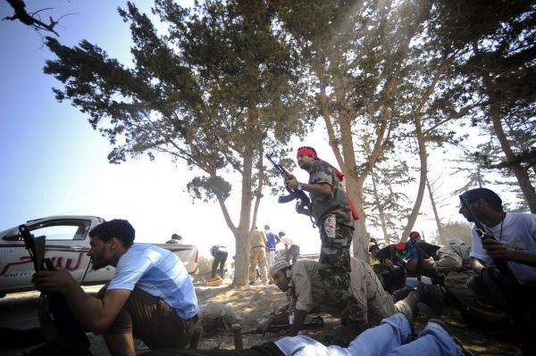 Rebels take position during fighting against regime forces west of Tripoli.