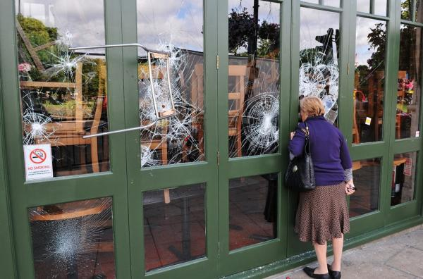 A chair is left embedded in a restaurant window on Aug. 9 following a night of rioting in the Haven Green area of Ealing, another suburb of London.