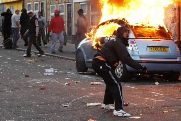 A rioter throws a rock at riot police in Hackney, London, on Aug. 8.