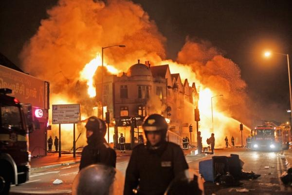 In the early hours of Aug. 9, firefighters in London battle a large fire that broke out in shops and residential properties. Looting and clashes with police continued for a third day in parts of the capital city after a fatal police shooting under disputed circumstances killed Mark Duggan, a 29-year-old father of four, on Aug. 4.