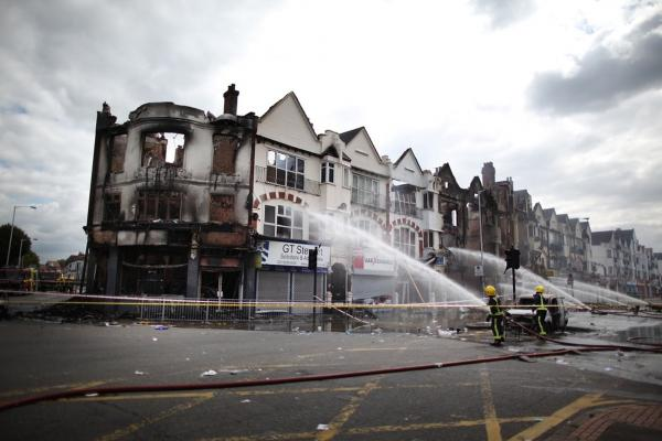 Firefighters damp smoldering buildings in the south London suburb of Croydon on Aug. 9. Emergency services have been cleaning up after three nights of rioting.