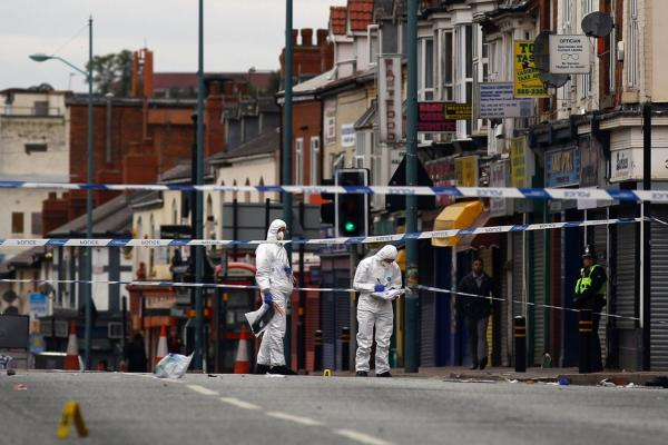 Police collect evidence at the scene where three people were killed after being struck by a vehicle in the Winson Green area on Aug. 10 in Birmingham, England. The three men were allegedly trying to protect local stores from looters.