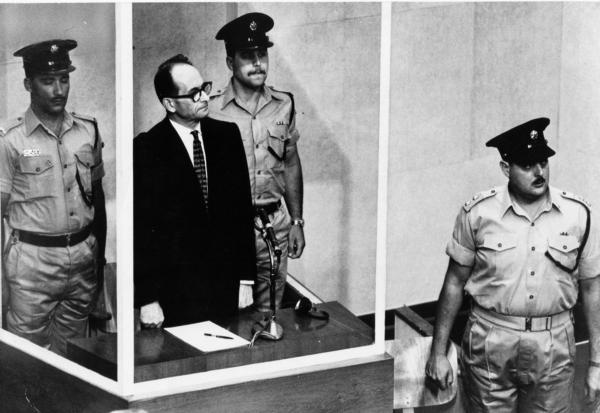 Adolf Eichmann stands in a bulletproof glass cage, flanked by guards, during his 1961 Nazi war crimes trial in Jerusalem. He was convicted of helping to exterminate Jews during World War II and sentenced to death.