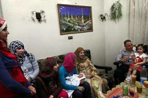 Diab (in yellow) sits with her sisters, husband and cousins after the Sebou. The ceremony has pagan roots, but has been adapted for modern times by Egyptian Muslims and Christians alike.