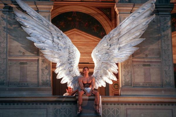 An employee adjusts the wings on a male model during Givenchy's 1997 spring/summer haute couture fashion collection by McQueen at a Paris show in January 1997.