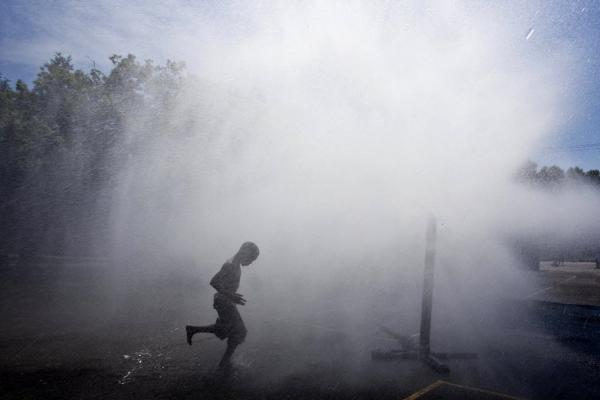 Jayson Hamler runs under a spray of water outside a school on Wednesday in Milwaukee.