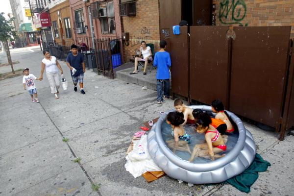 Stephanie Gracia (center) watches as her children and their friends cool off in an inflatable pool outside their apartment Thursday in Brooklyn.