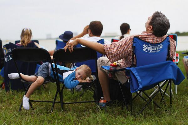 Zak Campbell (right) from San Diego, and his son Elijah sleep while awaiting the launch of space shuttle Atlantis in Cape Canaveral, Fla. It's the Campbells' first time attending a shuttle launch.