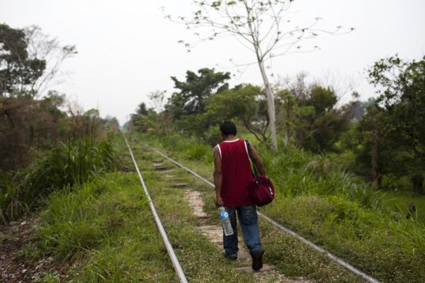 A Honduran migrant walks along the train tracks near Tenosique in the Mexican state of Tabasco. This is the beginning of a long journey across Mexico to the U.S. border.
