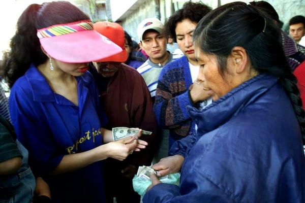 <b>ECUADOR, defaulted in 1999, 2008. </b> A woman exchanges Ecuadoran sucres for U.S. dollars at the Central bank in Quito in 2000. Ecuador switched to dollars after its currency devaluated greatly in 1999 and fell 23.5 percent in the first week of 2000.
