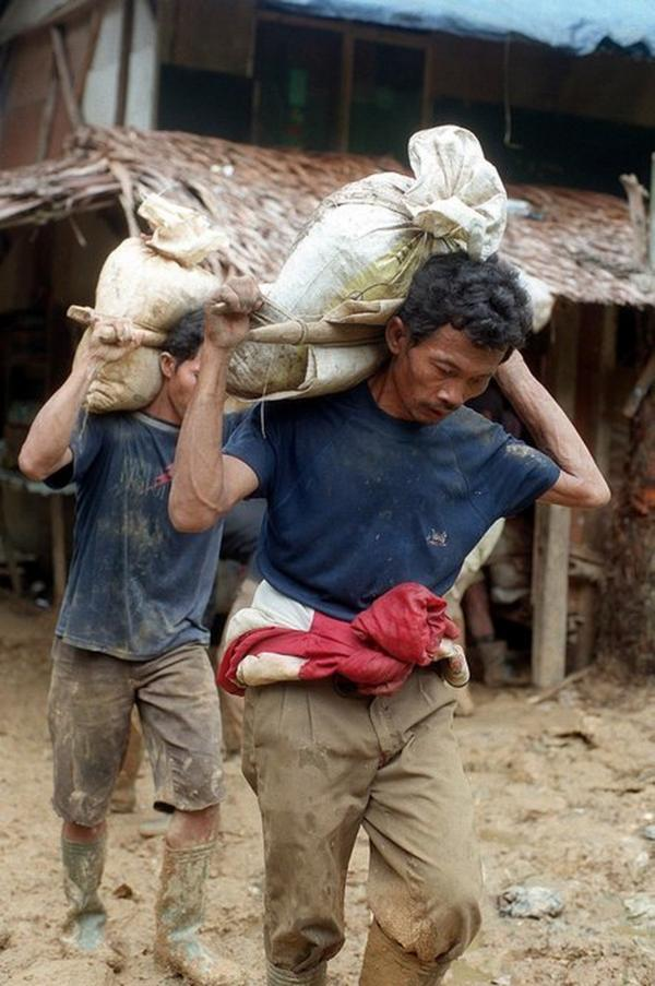 <b>INDONESIA, defaulted in 1998.</b> Indonesian miners carry bags of mud to be filtered for gold at the Aneka Tambang gold mining site in 1999. Hundreds of gold miners had been digging at the state-owned mining site without a permit since an economic crisis hit the country in 1997 and again the following year.