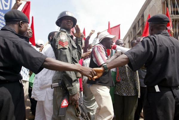 <b>NIGERIA, defaulted in 2002.</b> Police officers mount a barricade at the Labour Secretariat in Abuja to stop workers from marching in the street in 2004 amid continued economic woes. Nigerian trade unionists had gathered in the capital to protest rising fuel prices and mobilize support for an imminent general strike.