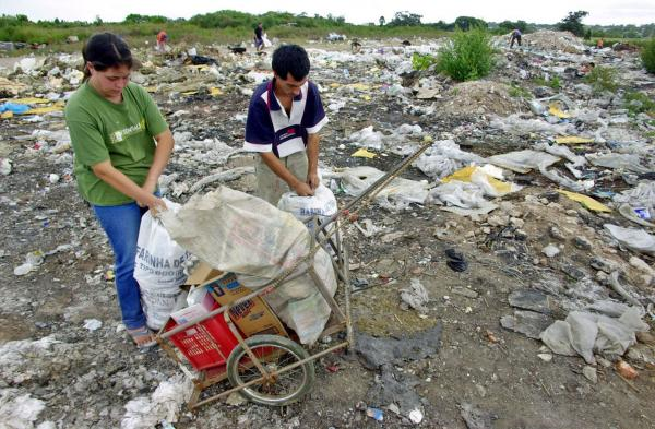 <b>URUGUAY, nearly defaulted in 2003. </b> Letisia Rodriguez, 18, and Ernesto Baez, 24, collect bottles, cardboard and food they find in a garbage dump in Montevideo. The economic crisis that affected Uruguay increased unemployment, forcing some Uruguayans to root through garbage to sustain their families.